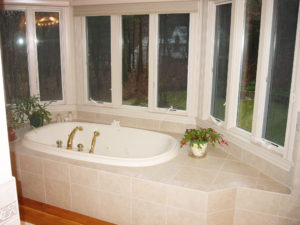 tiled jacuzzi tub surrounded by windows