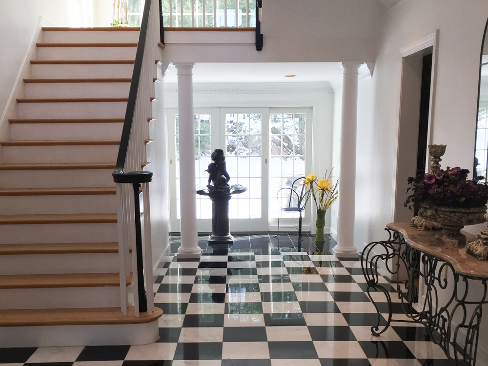 View of front french doors from the checker-floored foyer