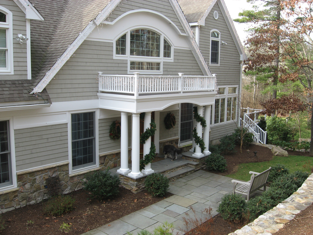 Another view of home front with balcony and columns around entrance