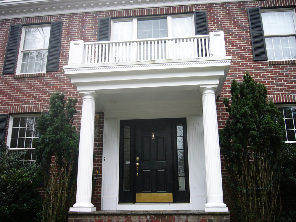 Entry way with columns and balcony - brick house