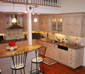 large beautiful kitchen tucked in under a balcony with white cabinets and granite counters.