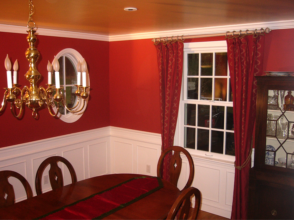 This dining room is so elegant with the traditional paneling, the many-paned window and the circular window!