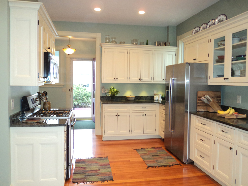 another view of whole kitchen - white cabinets, stainless steel, wood floors, grey granite