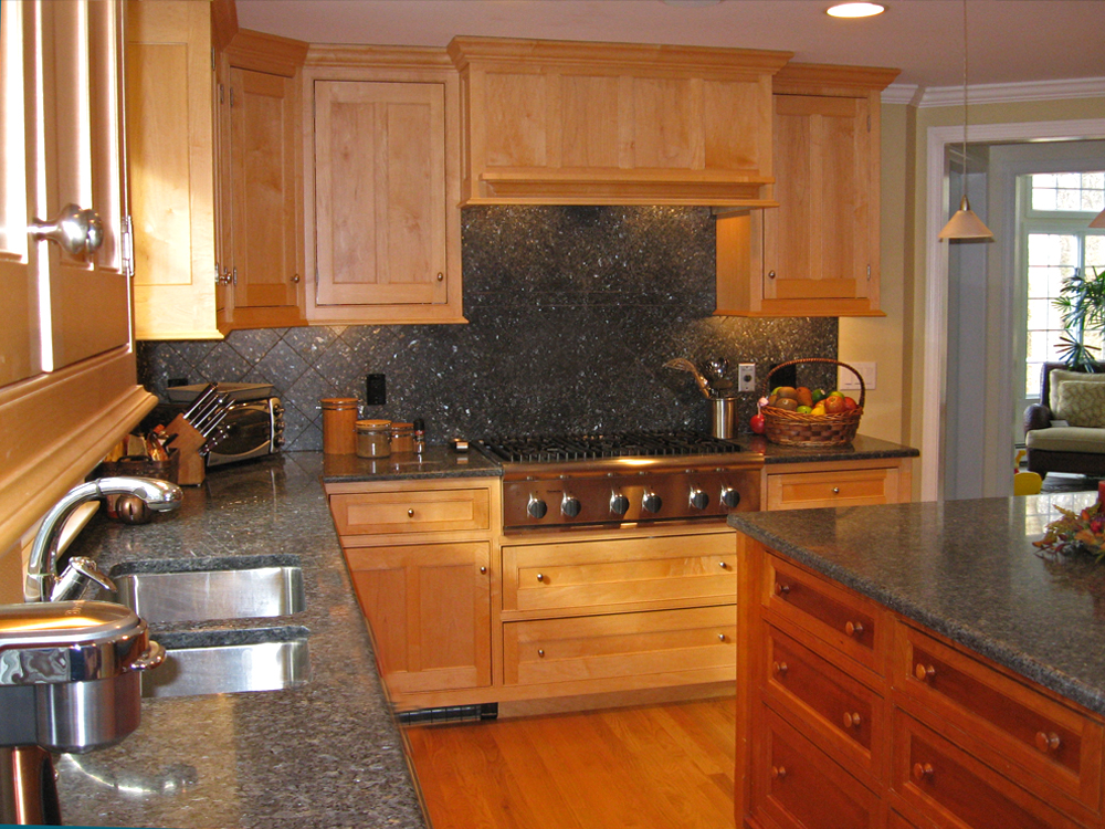 Lots of grey counters and blacksplash with cherry cabinets.