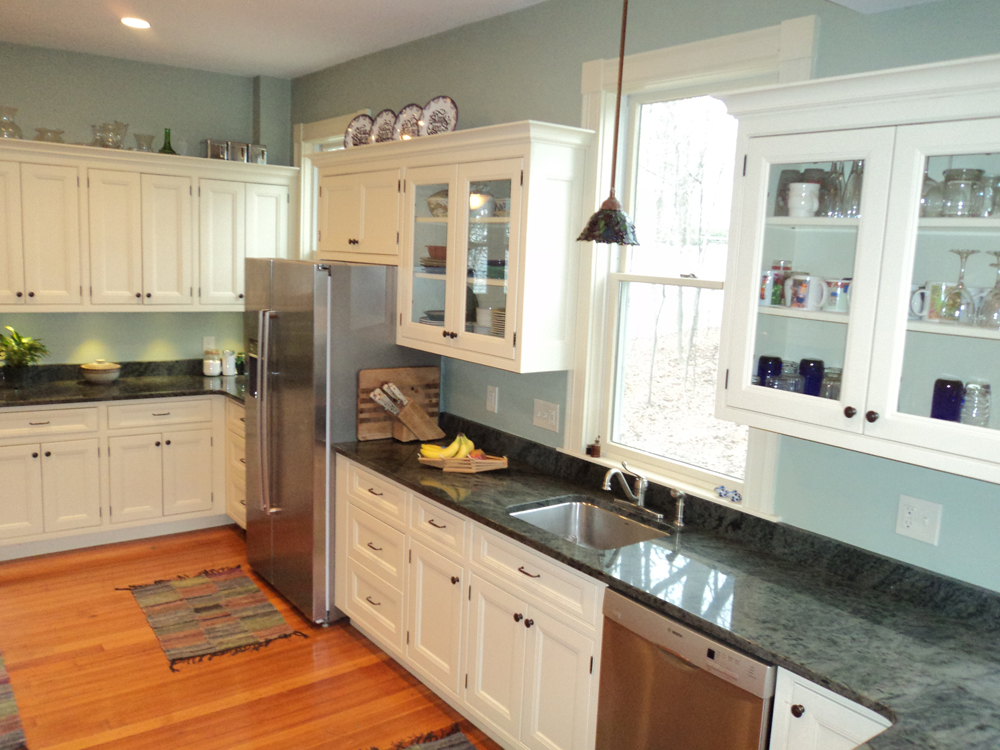 blue walls, glass cabinets, wood floors, and grey granite