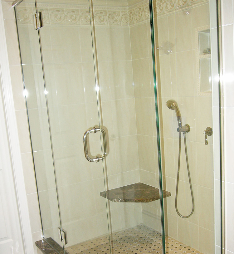 Love the seat and floor tiles in this beautiful shower! Don't miss the elegant tile trim at the top.