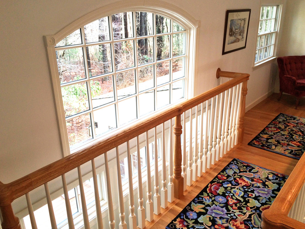 The complexity of this balcony space is just beautiful, with the curved large window letting in natural light, the detail of the beautiful wood and painted railings, and the warm wood floors.