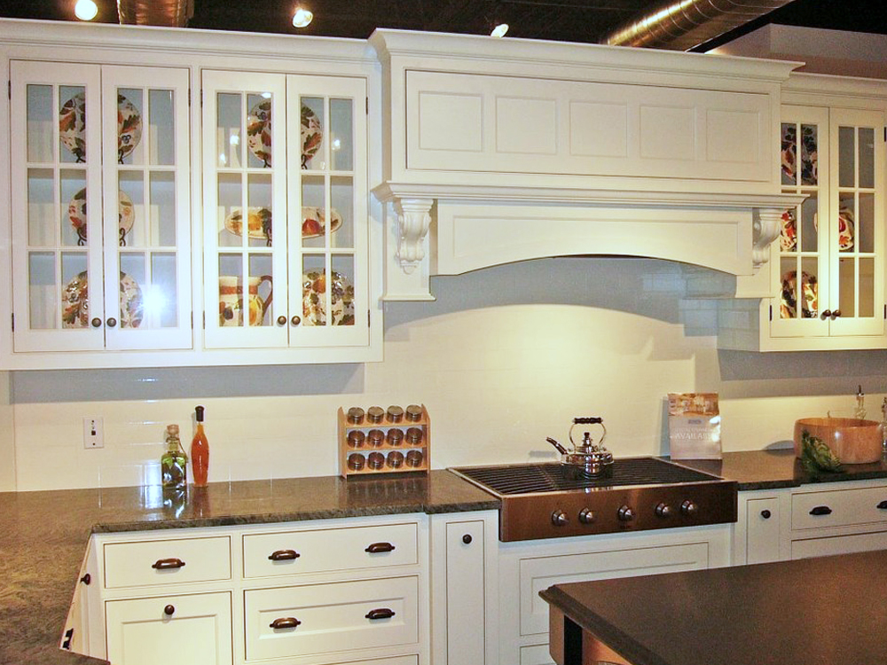 The details in this kitchen are amazing, from the carved supports over the stairs to the beautiful windowed cabinets! Custom kitchen by Don Wright!