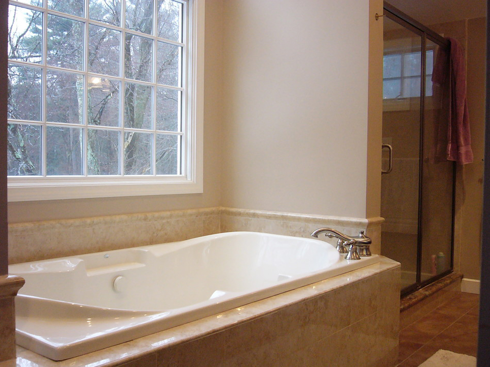Another beautifully crafted Jacuzzi tub, positioned under the window. Beautiful tile work.