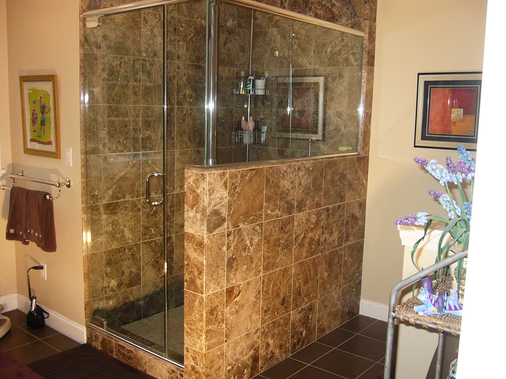 The stunning granite tiles combined with the glass door and window make this shower truly elegant.