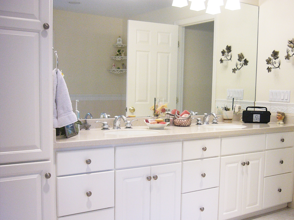 Perfect combo of cabinets, wall mirror and counters for a bright, clean bathroom.