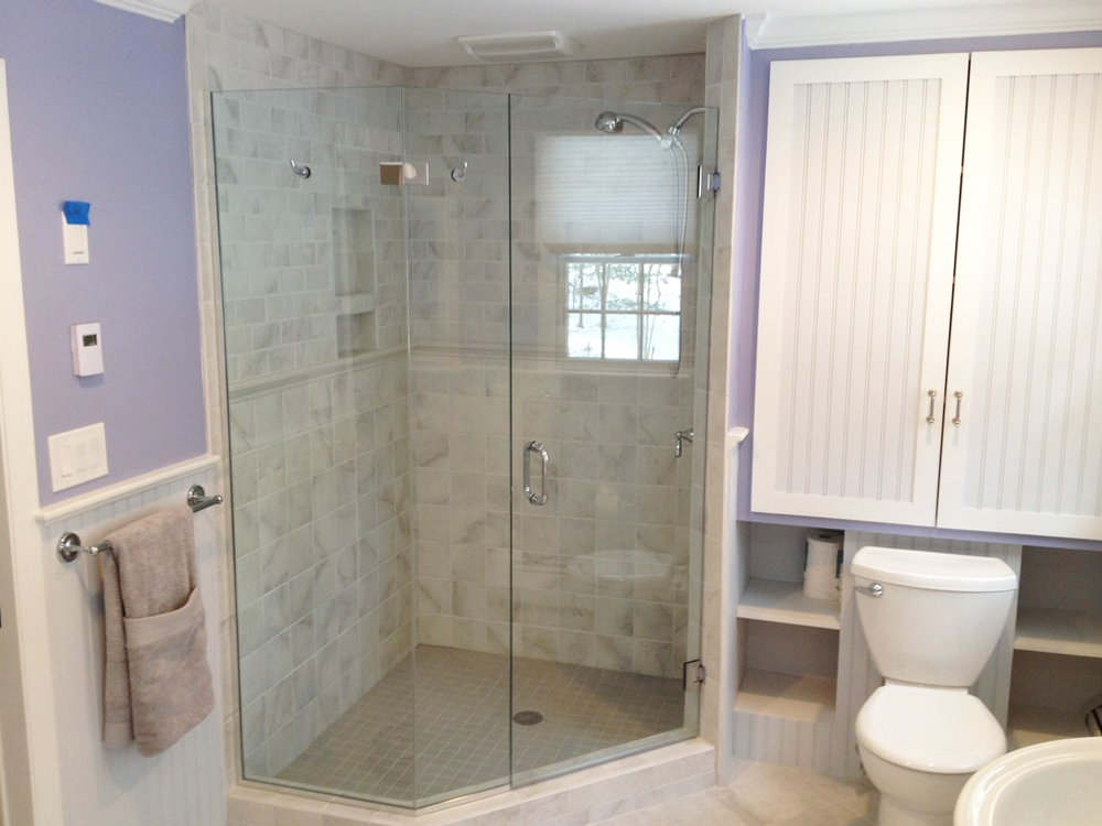 The beautiful glassed in shower and built in storage over the toilet create a beautiful and usable bathroom.